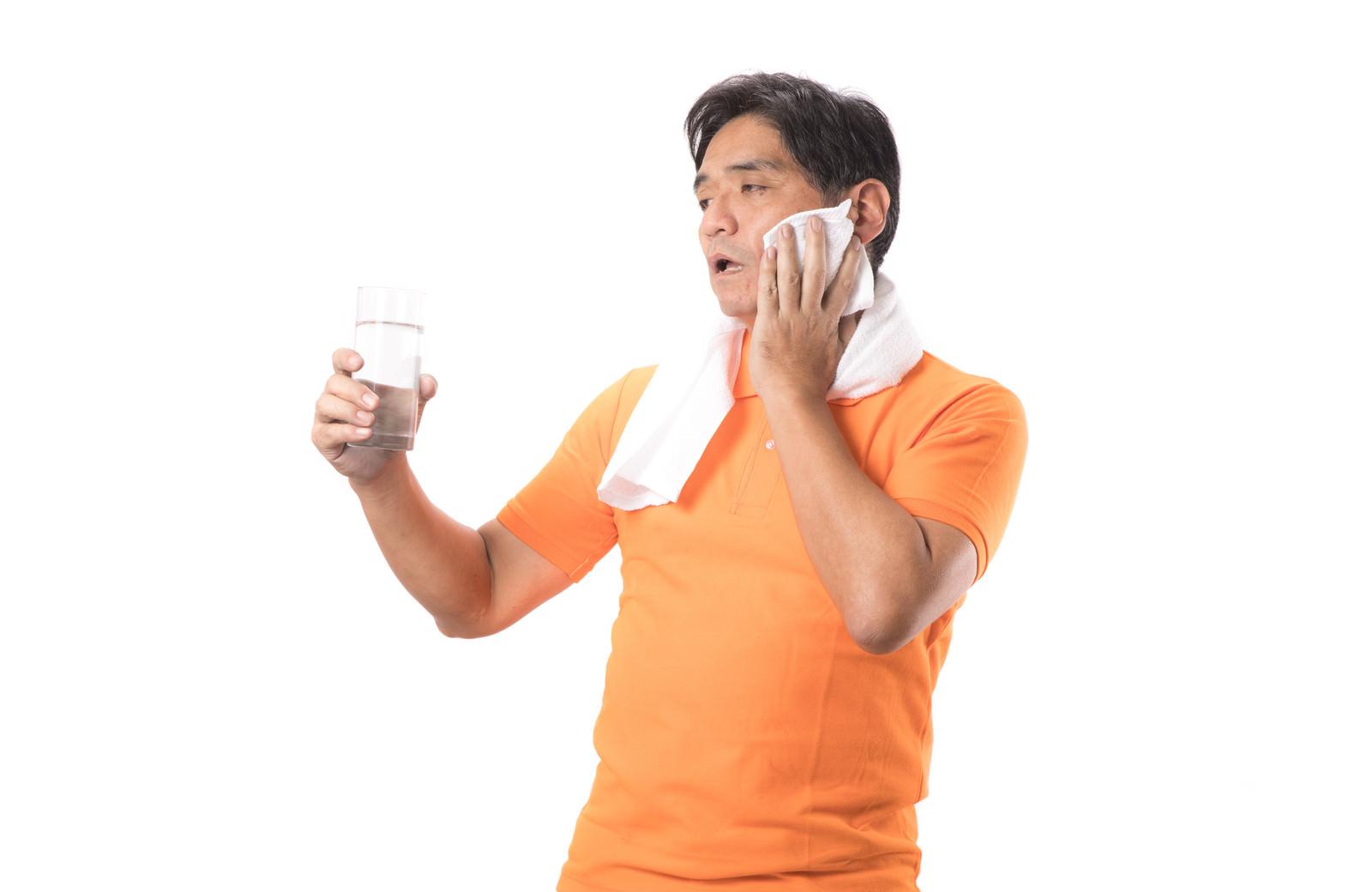 「運動のしすぎで熱中症気味の男性(水分補給)」の写真[モデル:よたか]