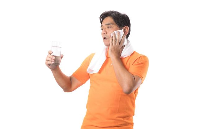 運動のしすぎで熱中症気味の男性(水分補給)の写真