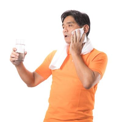 「運動のしすぎで熱中症気味の男性(水分補給)」の写真素材