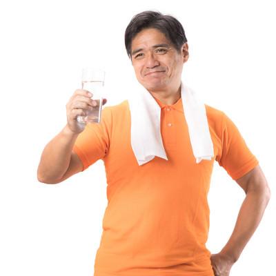「運動時も水分補給する中年男性」の写真素材