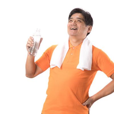 軽い運動後にペットボトルの水を飲む中年男性の写真