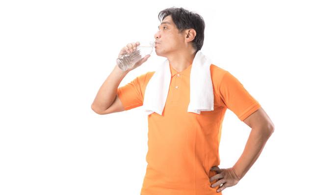 こまめにペットボトルの水を飲むランニングお父さんの写真
