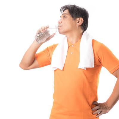 「こまめにペットボトルの水を飲むランニングお父さん」の写真素材