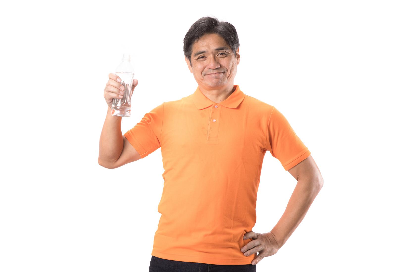 「水分補給にペットボトルを持ち歩く中年男性」の写真[モデル:よたか]