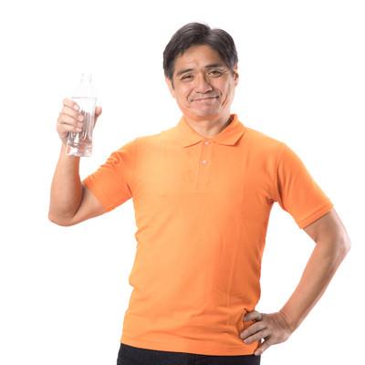 「水分補給にペットボトルを持ち歩く中年男性」の写真素材