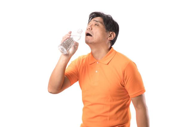 脱水症状で水を欲する中年男性の写真