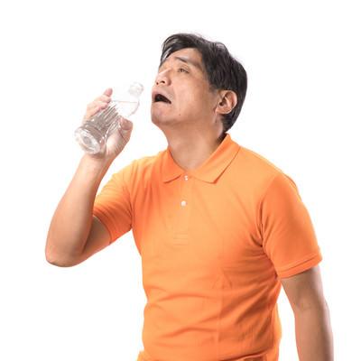 「脱水症状で水を欲する中年男性」の写真素材