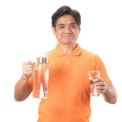ミネラルウォーターを手に持った笑顔の中年男性の写真