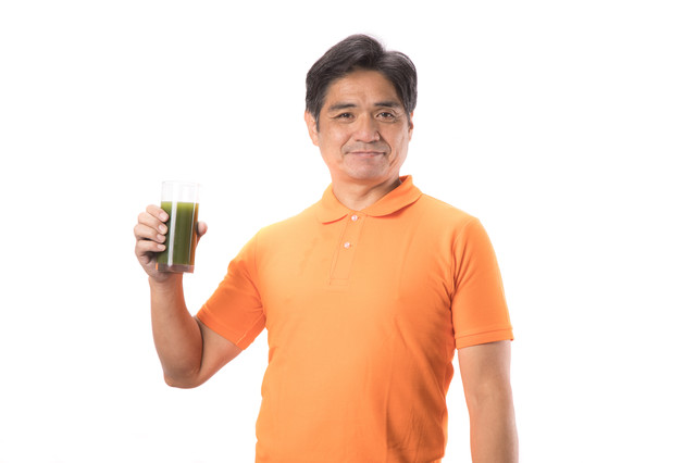青汁を片手に持った中年男性の写真