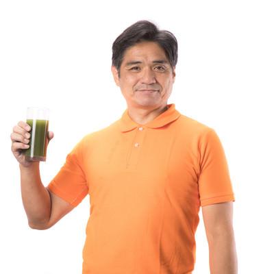 「青汁を片手に持った中年男性」の写真素材