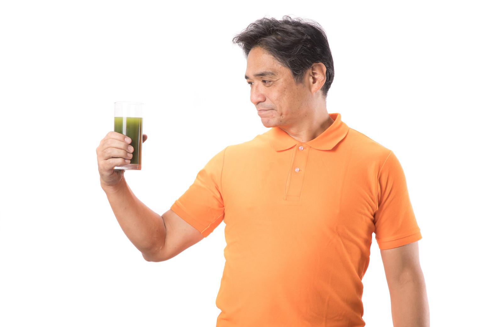 「青汁を見つめる中年の男性」の写真[モデル:よたか]