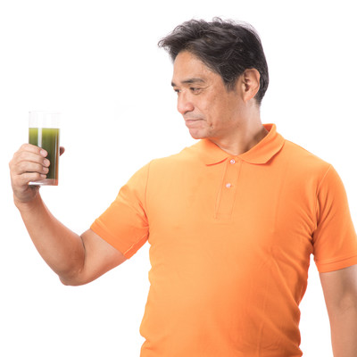 青汁を見つめる中年の男性の写真
