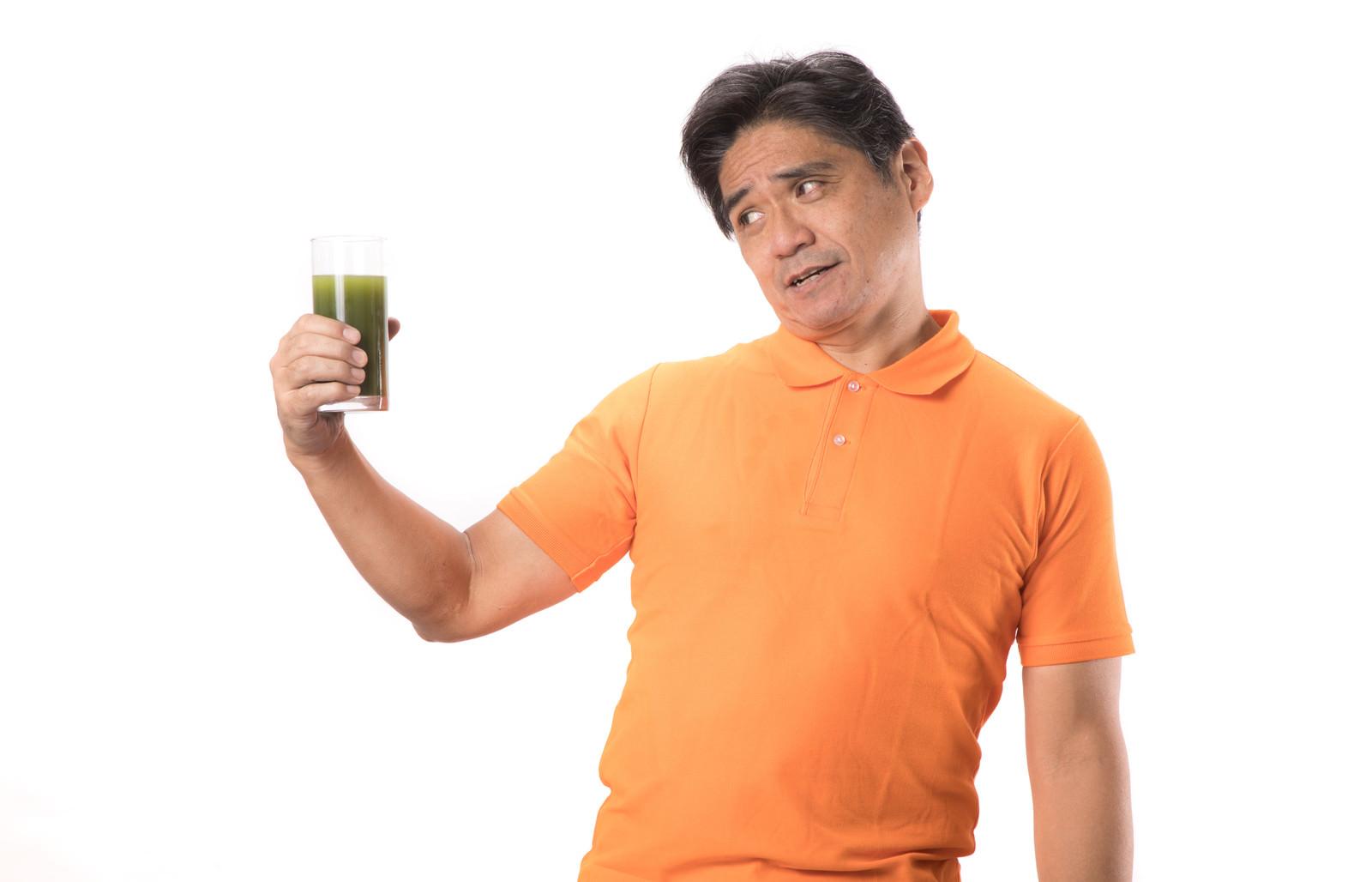 「苦い青汁を見て顔がひきつる中年男性」の写真[モデル:よたか]