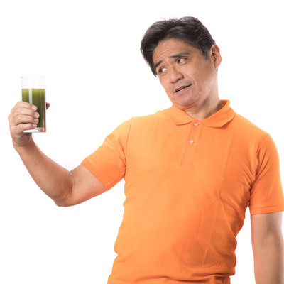 「苦い青汁を見て顔がひきつる中年男性」の写真素材