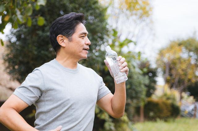 屋外でミネラルウォーターを飲む中年男性の写真