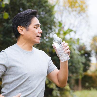 「屋外でミネラルウォーターを飲む中年男性」の写真素材