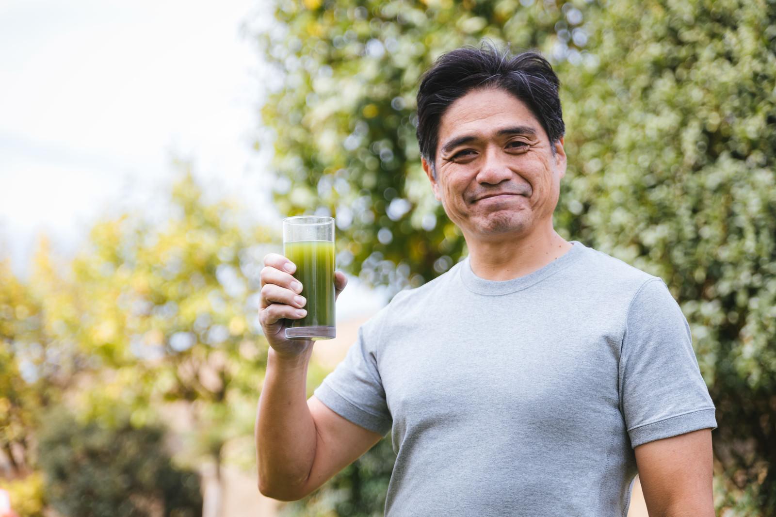 「屋外で健康的に青汁を飲むお父さん」の写真[モデル:よたか]