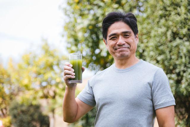 屋外で健康的に青汁を飲むお父さんの写真
