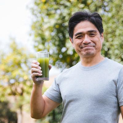 「屋外で健康的に青汁を飲むお父さん」の写真素材