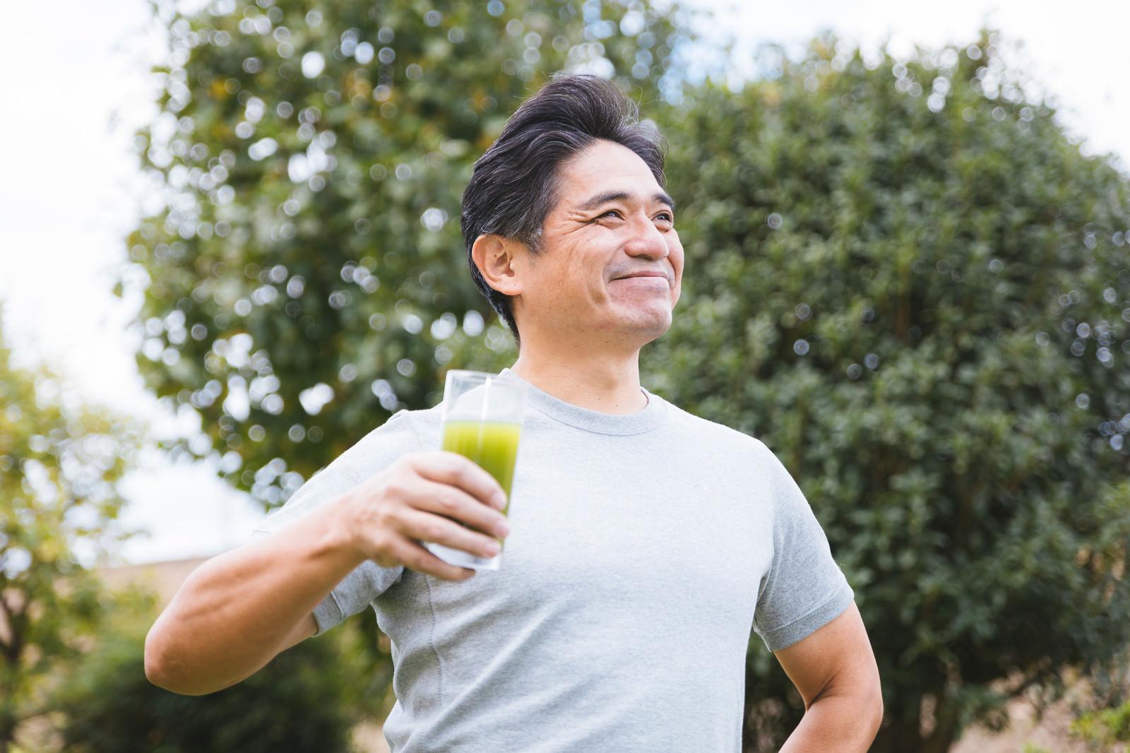 「屋外で青汁を飲む中年男性」の写真[モデル:よたか]