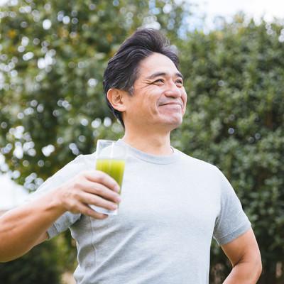 「青汁が入ったコップを握りしめる健康体の中年男性」の写真素材