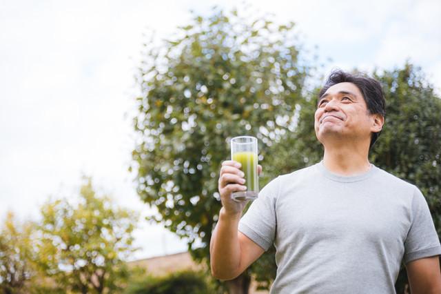 庭で青汁を飲むお父さんの写真