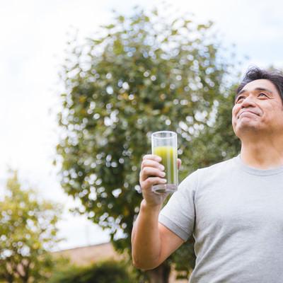「庭で青汁を飲むお父さん」の写真素材