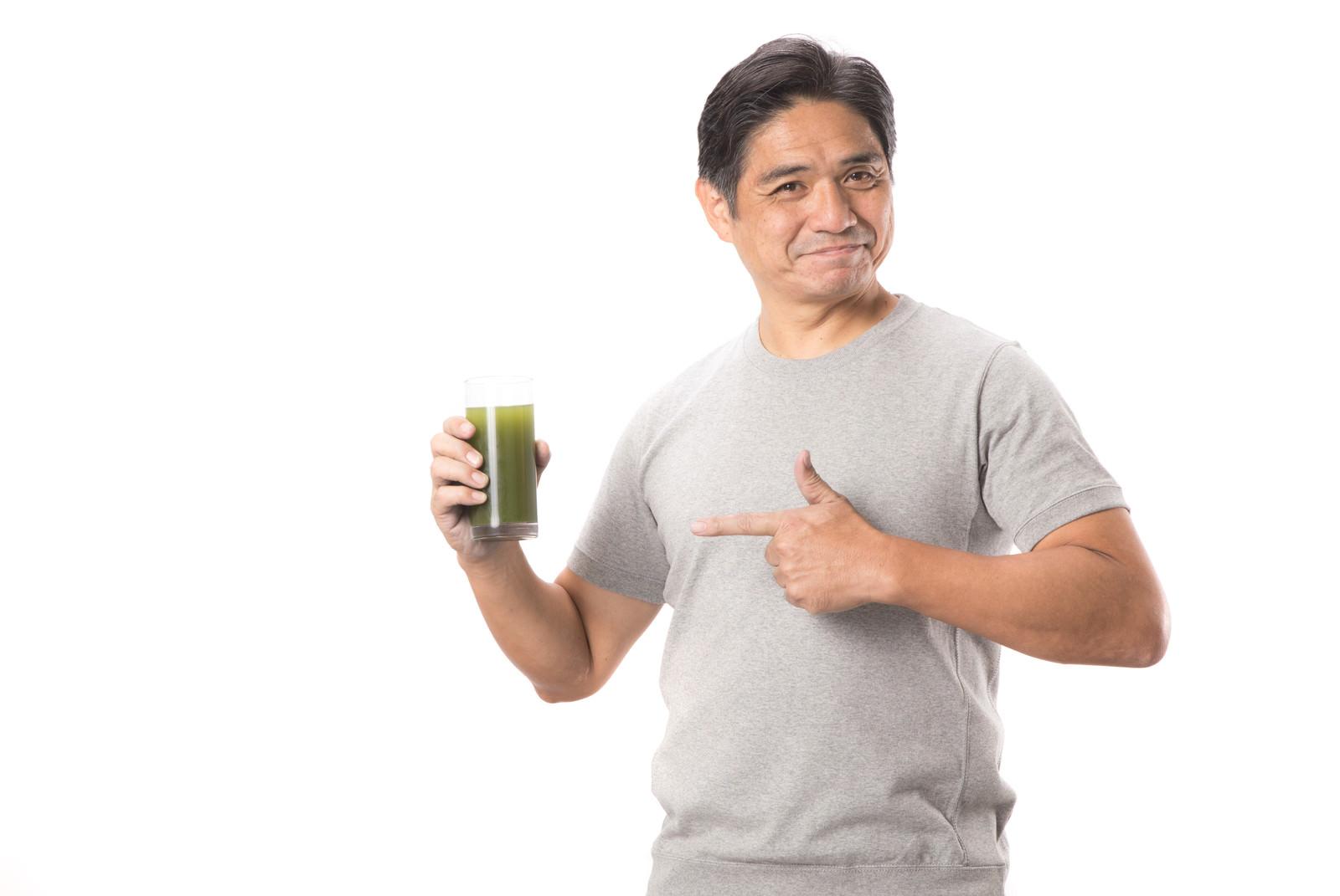 「グラスの青汁を指差す中年男性」の写真[モデル:よたか]