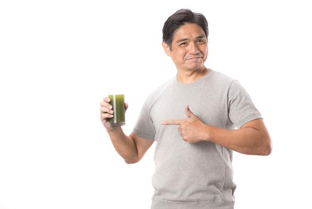 グラスの青汁を指差す中年男性の写真