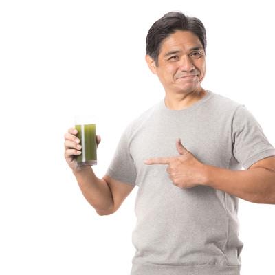 「グラスの青汁を指差す中年男性」の写真素材