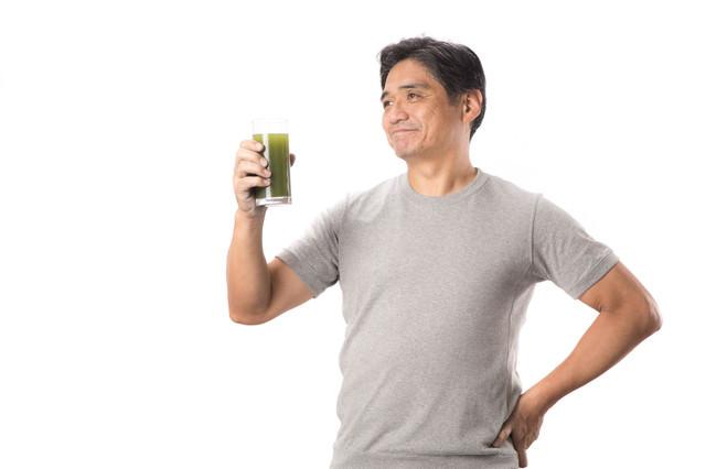 栄養豊富の青汁と健康を気にする中年男性の写真