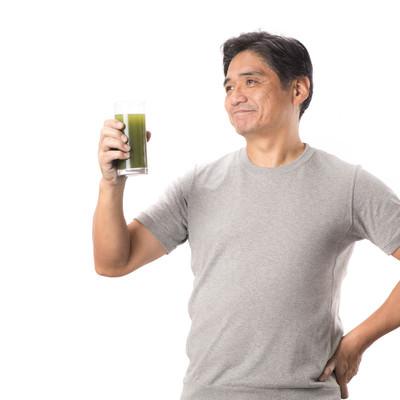 「栄養豊富の青汁と健康を気にする中年男性」の写真素材