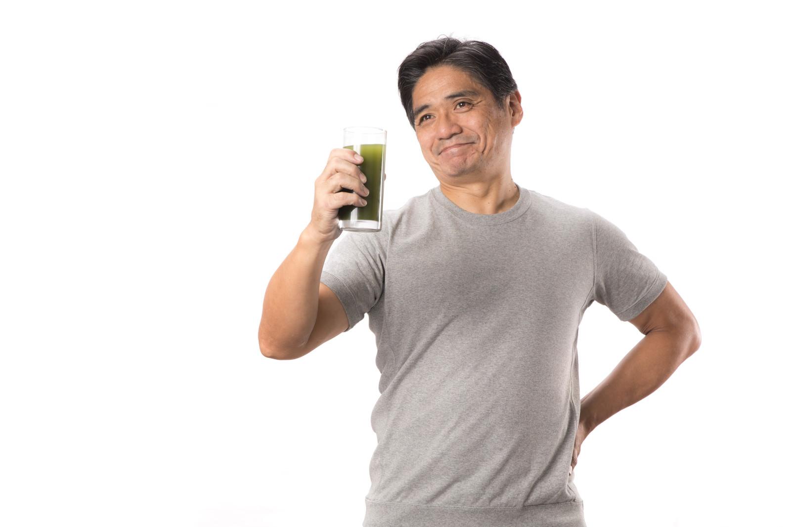 「青汁が入ったコップを片手に笑顔のお父さん」の写真[モデル:よたか]