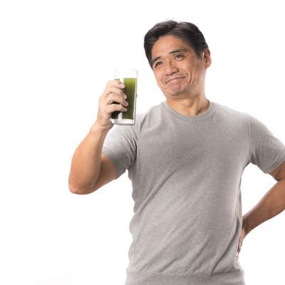 「青汁が入ったコップを片手に笑顔のお父さん」の写真素材
