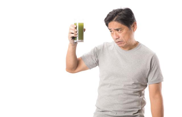 「勧められた青汁を手に取る中年男性」のフリー写真素材