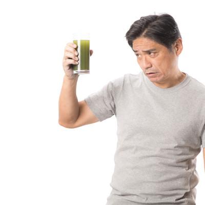 「勧められた青汁を手に取る中年男性」の写真素材