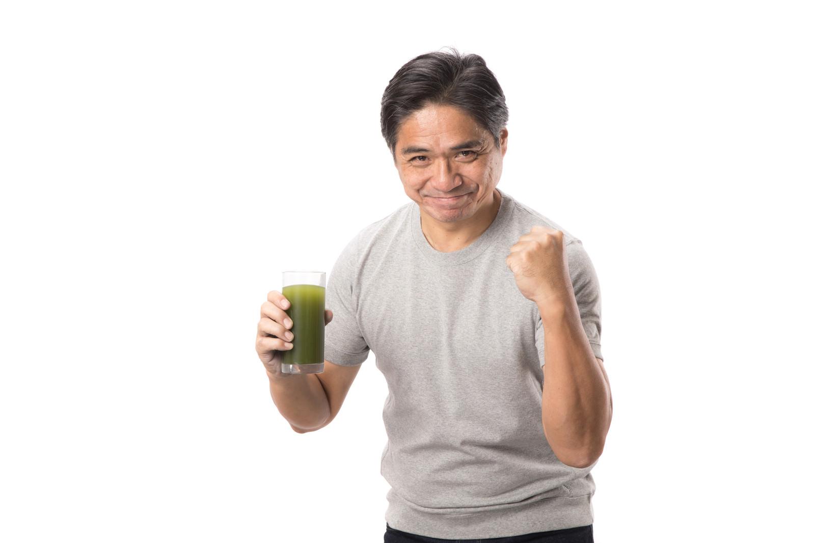 「青汁ガッツをキメる中年男性」の写真[モデル:よたか]
