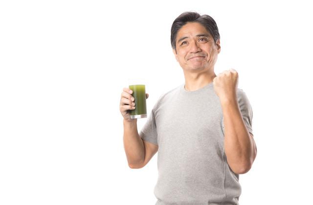 青汁を片手にガッツポーズ中年の写真