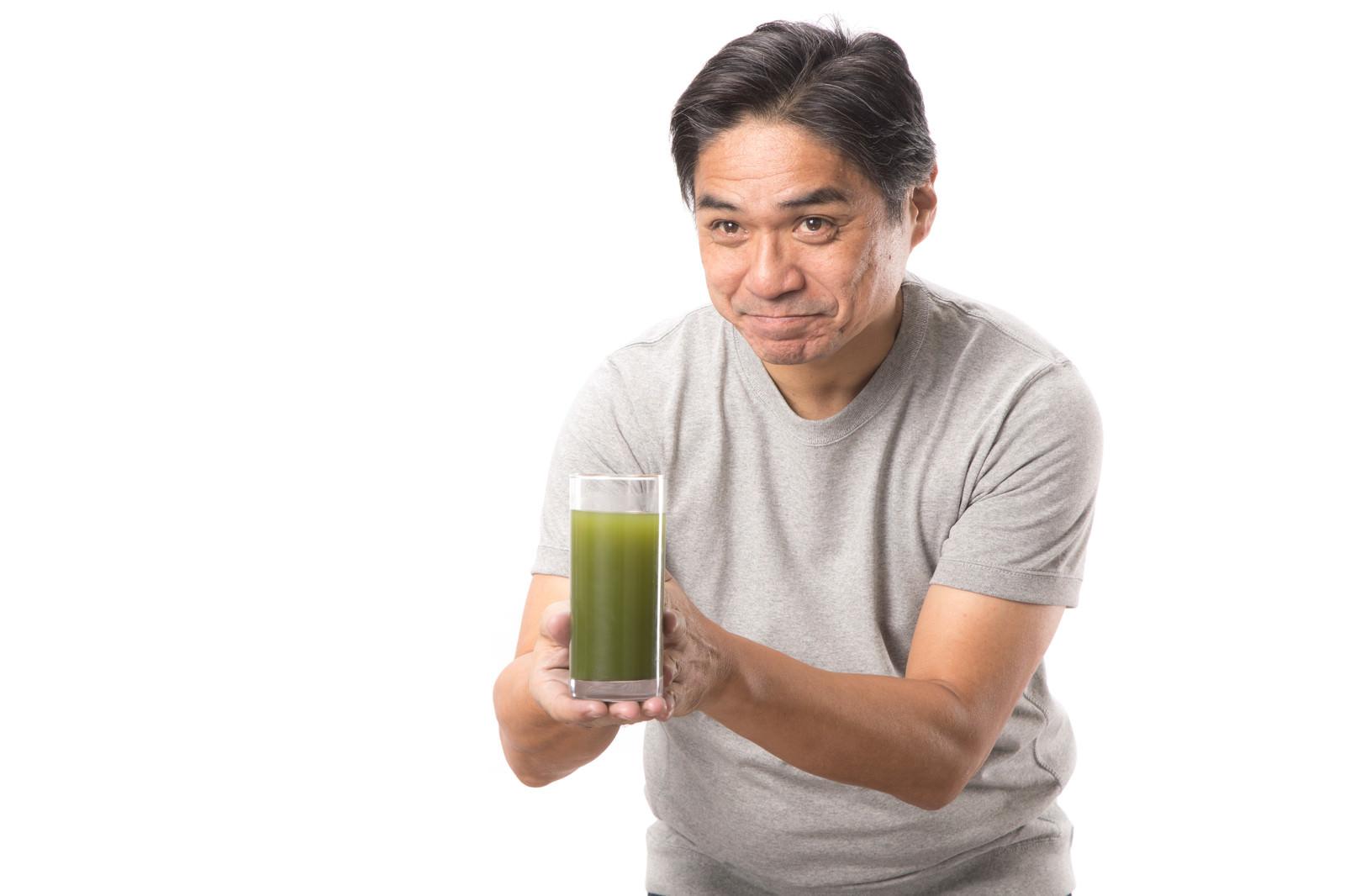「搾りたての青汁をお持ちしました(中年男性)搾りたての青汁をお持ちしました(中年男性)」[モデル:よたか]のフリー写真素材を拡大