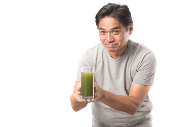 「搾りたての青汁をお持ちしました(中年男性)」のフリー写真素材