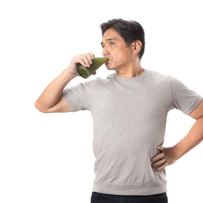 健康的に青汁を飲む中年のおじさんの写真