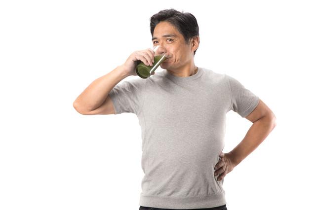 健康的に青汁を飲む中年男性の写真