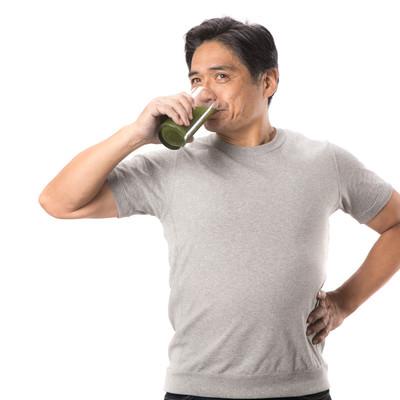 「健康的に青汁を飲む中年男性」の写真素材