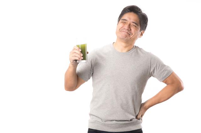 「青汁を飲んでこぼれる笑顔(中年男性)」のフリー写真素材