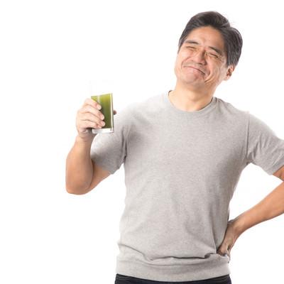 「青汁を飲んでこぼれる笑顔(中年男性)」の写真素材