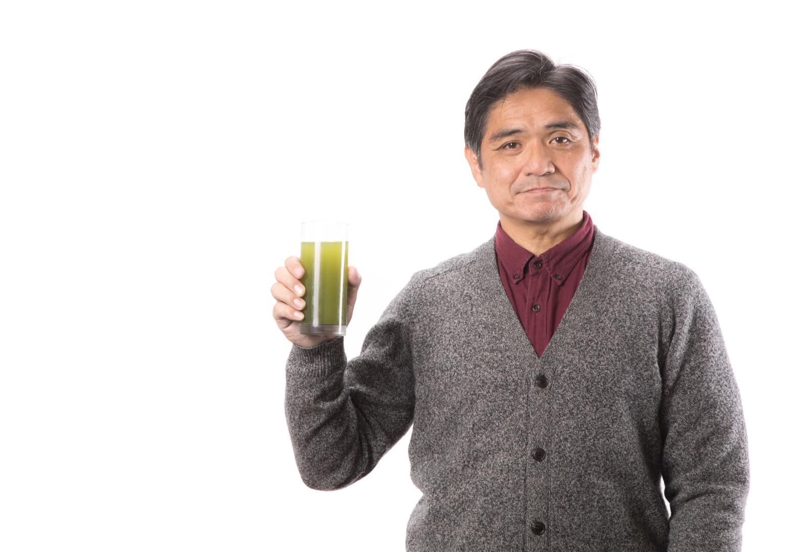「青汁で健康をアピールする中年男性」の写真[モデル:よたか]