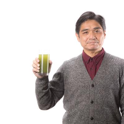 青汁で健康をアピールする中年男性の写真