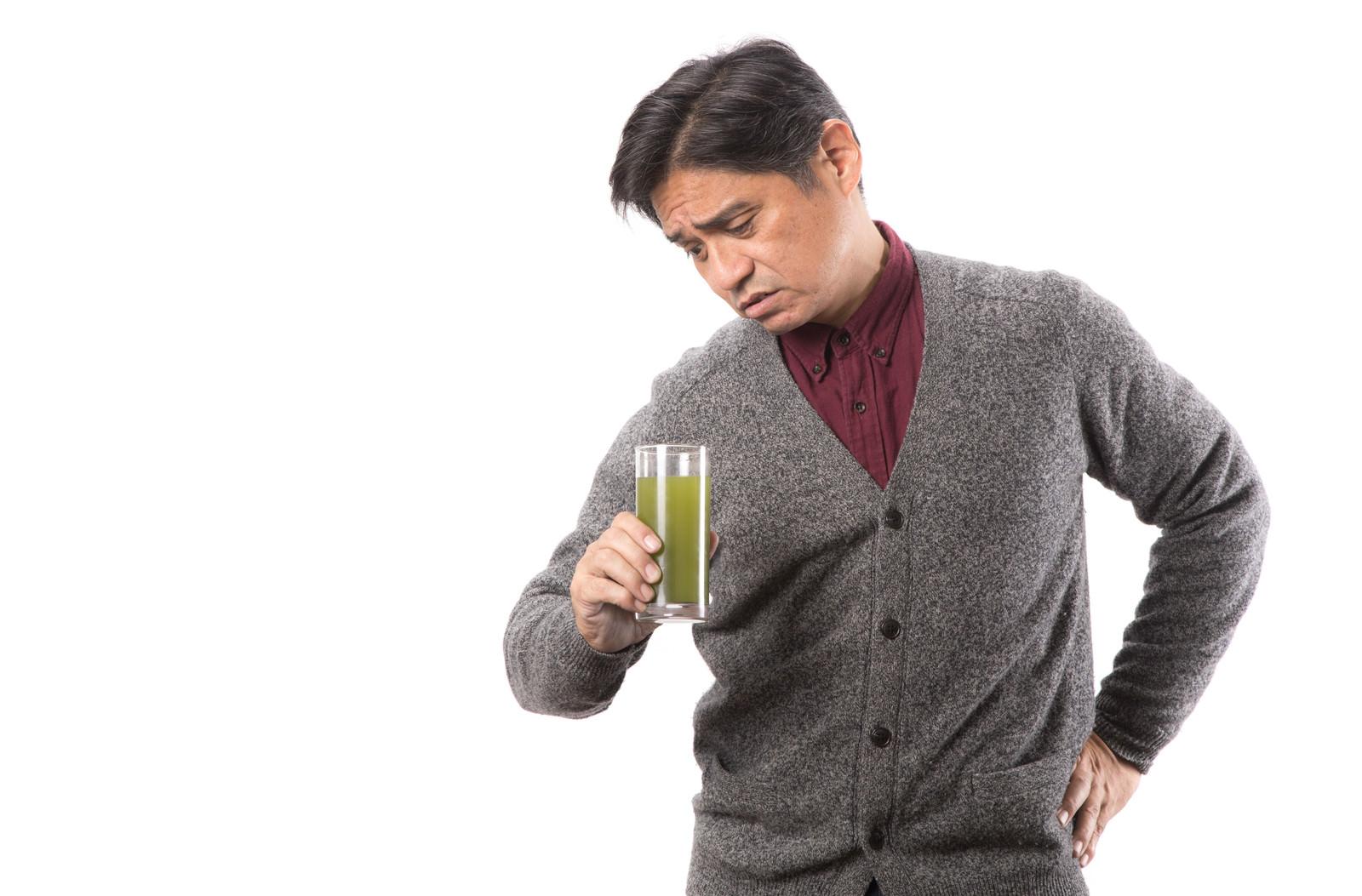 「コップに入った青汁を覗き込む中年男性」の写真[モデル:よたか]