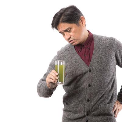 「コップに入った青汁を覗き込む中年男性」の写真素材