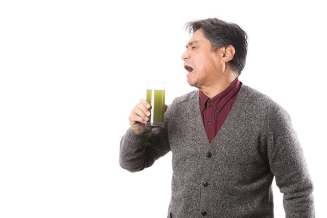 苦くて濃い青汁を飲んで渋い顔をする中年男性の写真